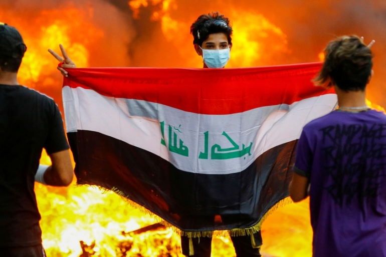 A demonstrator carries an Iraqi flag during ongoing anti-government protests in Baghdad [Thaier al-Sudani/Reuters]