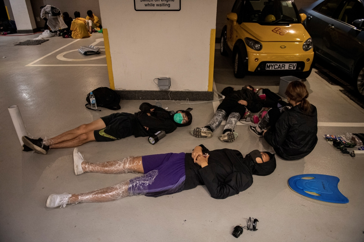 PolyU protesters resting on the floor. [Nicolas Asfouri/AFP]