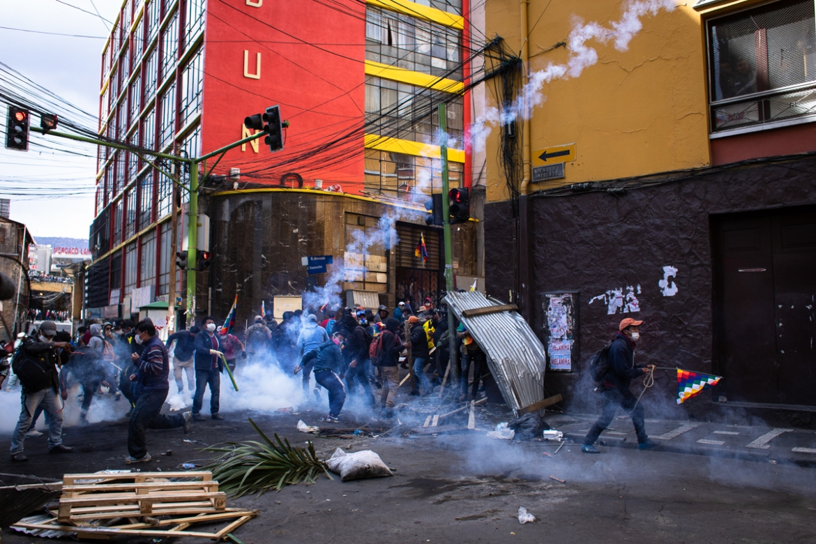 Protesters throw tear gas canisters back at the police after tearing down a barricade during demonstrations in support of former President Evo Morales. [Erika Pineros/Al Jazeera]