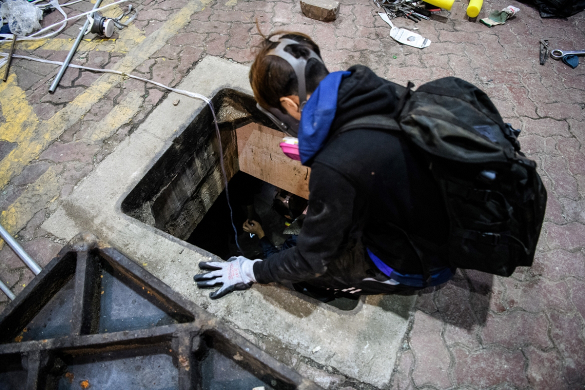 A protester climbs down into a sewer as he and others try to find an escape route from the campus. [Anthony Wallace/AFP]