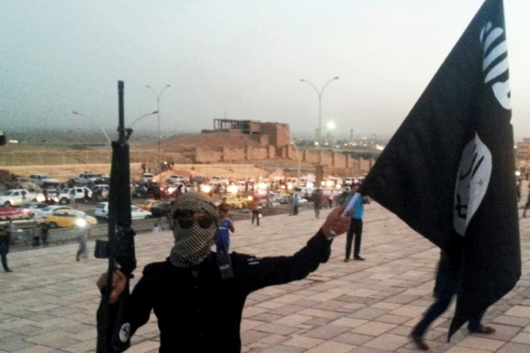 A fighter of the Islamic State of Iraq and the Levant  holds an black flag and a weapon on a street in the city of Mosul, Iraq June 23, 2014 [Reuters]