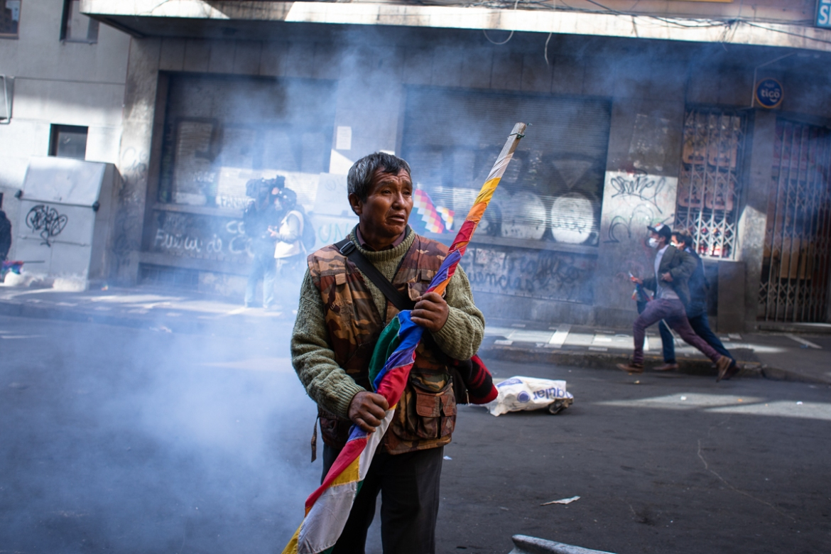A man stands with the Wiphala, the indigenous flag, amid the tear gas during a demonstration that turned violent in La Paz. [Erika Pineros/Al Jazeera]