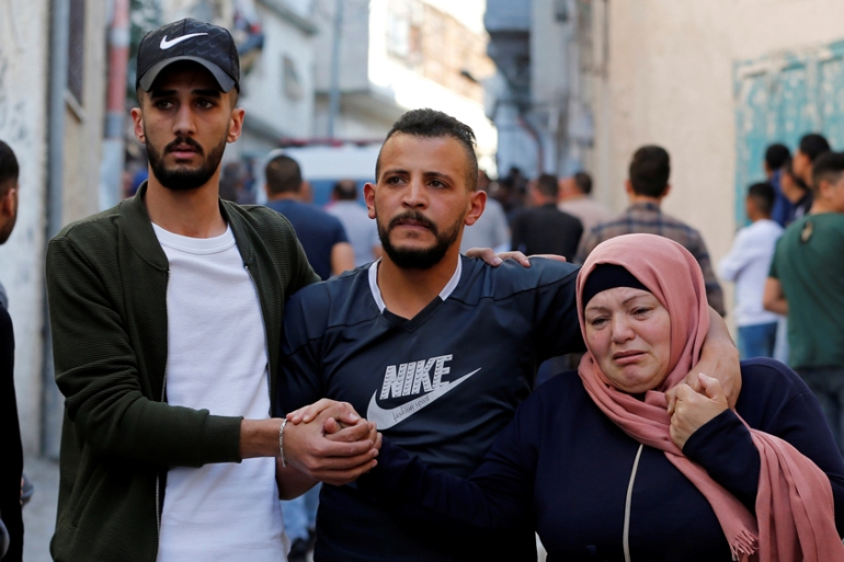 Relatives of a Palestinian man killed grieve during his funeral in al-Arroub refugee camp on Monday [Mussa Qawasma/Reuters]