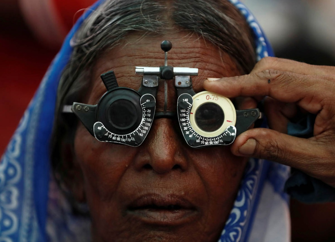 A woman gets her eyes tested at a free eye-care camp on the occasion of Indian leader Babasaheb Ambedkar's death anniversary in Mumbai, India. [Francis Mascarenhas/Reuters]
