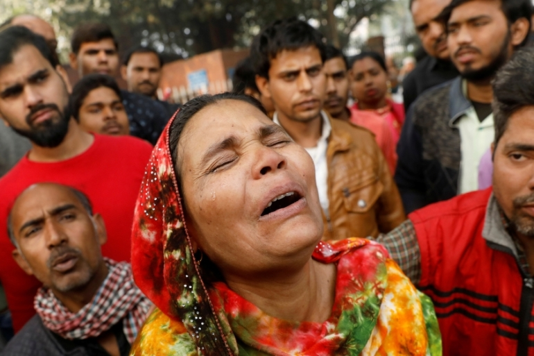 A relative of a victim of the blaze that swept through the factory where labourers were sleeping cries outside a hospital mortuary in New Delhi [Adnan Abidi/Reuters]