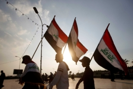 Demonstrators carry Iraqi flags during continuing anti-government protests in Basra, Iraq [Essam al-Sudani/Reuters]