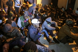 Migrants sit on the floor at a detention centre in Libya's Tajoura, in the eastern suburbs of the capital Tripoli [File: Mahmud Turkia/AFP]