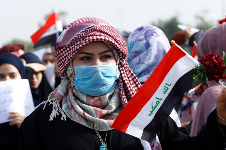 An Iraqi university student holds an Iraqi flag during continuing anti-government protests in Najaf, Iraq [Alaa al-Marjani/Reuters]