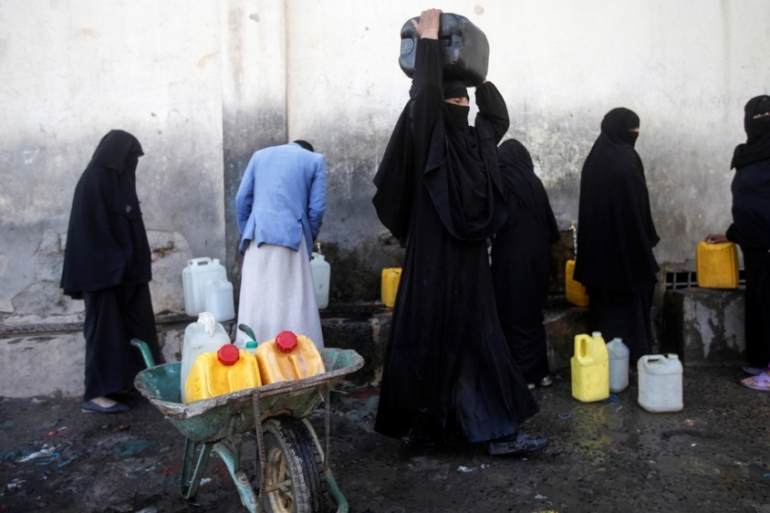 People collect water amid a shortage of supplies in the capital Sanaa [Mohamed al-Sayaghi/Reuters]