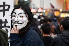 A protester wears a Guy Fawkes mask at a march in Hong Kong [Laurel Chor/Reuters]