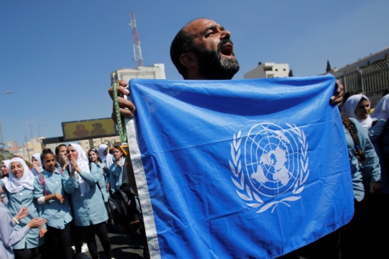 A Palestinian demonstrator holds a UN flag during a rally against a US decision to cut funding to the United Nations Relief and Works Agency (UNRWA) on  September 26, 2018 [Reuters/Mussa Qawasma]