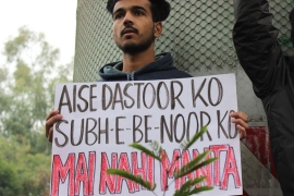 A protester in New Delhi holds a poster carrying the famous lines by Pakistani poet Habib Jalib [Bilal Kuchay/Al Jazeera]