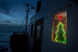 A Christmas tree light in the window of the Alan Kurdi rescue ship [Sally Hayden/Al Jazeera]