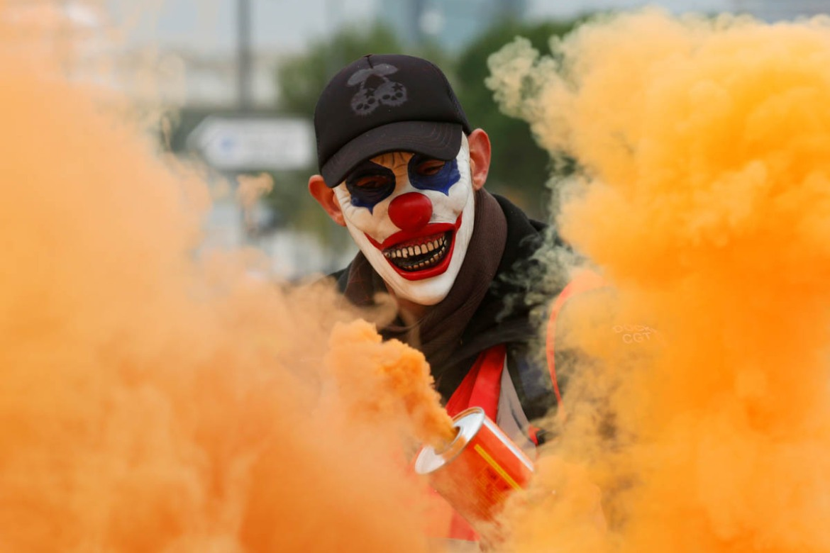 A protester wearing a mask is seen among smoke as French workers demonstrate against the government's pension reform plans in Marseille as part of a day of national strike and protests. [Jean-Paul Pelissier/Reuters]