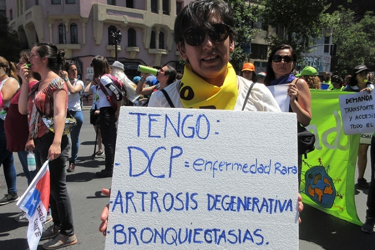 At a protest in Santiago, Maria Soledad Guerra holds a sign with her diagnosed rare genetic disorder [Sandra Cuffe/Al Jazeera]