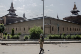 An Indian paramilitary soldier patrols outside the Jamia Masjid, or Grand Mosque, in Srinagar [Dar Yasin/AP]