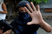 A young member of Barrio-18 gang gestures as he holds a gun in San Pedro Sula, Honduras, September 28, 2018 [File: Goran Tomasevic/Reuters]