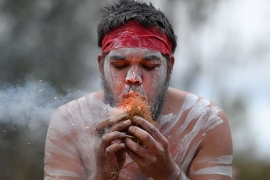 An Aboriginal dancer lights a fire during a traditional dance [File: Dan Peled/EPA]