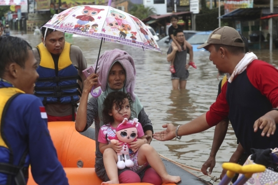 About 120,000 rescuers had been deployed to evacuate those affected and install mobile water pumps as more downpours were forecast in coming days [Achmad Ibrahim/AP]