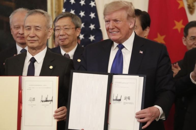 Chinese Vice Premier Liu He, left, and US President Donald Trump, right, hold signed copies of the US-China phase one trade agreement in Washington, DC [File: Zach Gibson/Bloomberg]