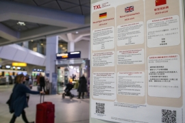 Information in German, English and Chinese languages about the Novel Coronavirus 2019-nCoV are on display at the Tegel airport in Berlin on January 26, 2020 [Andreas Gora/dpa/AFP]