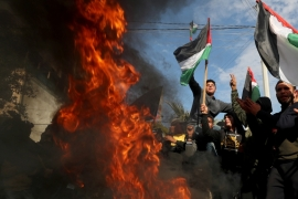 Palestinians protest as tyres burn ahead of the announcement by US President Donald Trump of his long-delayed Middle East plan, in Gaza City [Mohammed Salem/Reuters]