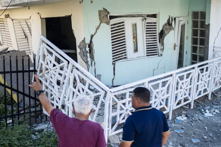 People pass by a house damaged by an earthquake in Guanica, Puerto Rico [Ricardo Arduengo/AFP]