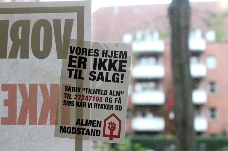 Windows in Mjolnerparken are covered in stickers from Almen Modstand, a group organising against forced re-locations. The stickers read: 'Our home is not for sale!' [Jamila Versi/Al Jazeera]