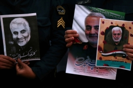 Iranian guards hold a picture of General Qassem Soleimani, during a protest against his killing, in front of the UN office in Tehran, on  January 3, 2020 [WANA/Nazanin Tabatabaee via Reuters]