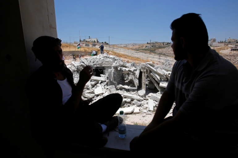Men watch as a Palestinian house is demolished by Israeli forces in Sur Baher village [File: Mussa Qawasma/Reuters]
