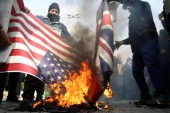 Demonstrators burn American and British flags during a protest against the assassination of the Iranian Major-General Qassem Soleimani in Tehran on January 3, 2020 [WANA via Reuters]