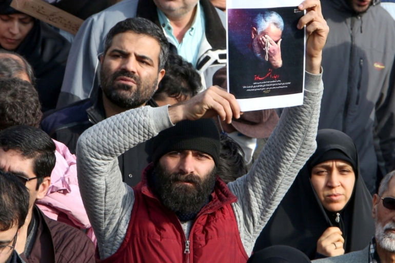 A man holds a picture of slain Iranian Revolutionary Guards Major General Qassem Soleimani during a demonstration in Tehran on January 3, 2020 [Atta Kenare/AFP]