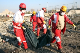 Members of the International Red Crescent collect bodies of victims around the wreckage after an Ukraine International Airlines Boeing 737-800 carrying 176 people crashed near Imam Khomeini Airport in Tehran, killing everyone on board [File: Abedin Taherkenareh/EPA]
