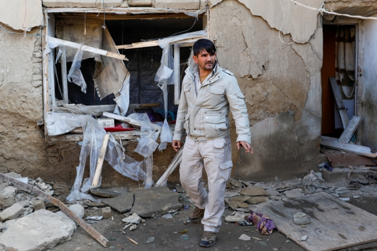 A man inspects a damaged house at the site of an attack at a US military airbase in Bagram, north of Kabul [File: Mohammad Ismail/Reuters]