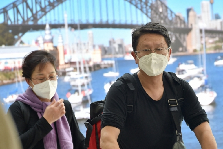 Passengers wearing masks arrive at Sydney airport after landing on a plane from Wuhan on Thursday [Peter Parks/AFP]