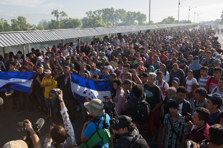 Hundreds of migrants and asylum seekers gather at the border crossing into Mexico on January 18 [Jeff Abbott/Al Jazeera]