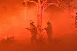 This picture taken on December 31, 2019, shows firefighters struggling against strong winds and flying embers in an effort to secure nearby houses from bushfires near the town of Nowra in the Australian state of New South Wales [Saeed Khan/AFP]