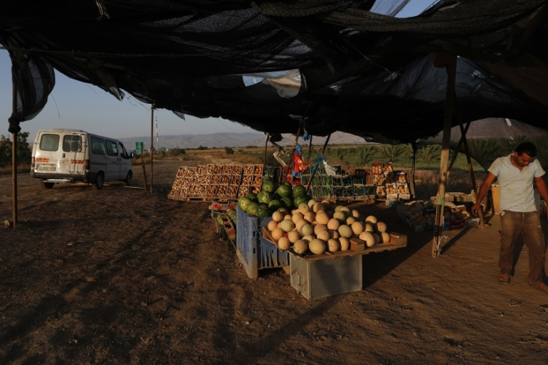 A Palestinian vendor sells his vegetables products next to route 90 in the Jordan valley [File: Atef Safadi/EPA]