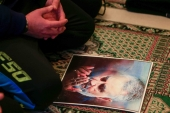 A man prays next to a picture of Iranian General Qassem Soleimani, head of the elite Quds Force, inside a mosque in Ghazieh, south of Lebanon on January 3, 2020 [Reuters/Ali Hashisho]
