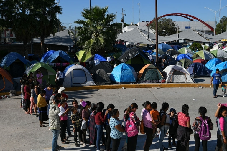 Migrants, most of them asylum seekers sent back to Mexico from the US under the 'Remain in Mexico' programme, officially named Migrant Protection Protocols, wait in line for a meal outside the Human Repatriation office in Matamoros, Tamaulipas, Mexico [File: Loren Elliott/Reuters]