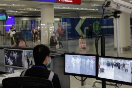 A health surveillance officer monitors passengers arriving at the Hong Kong International airport in Hong Kong following the reports of the spread of viral pneumonia illness in and around China [File: Andy Wong/AP]