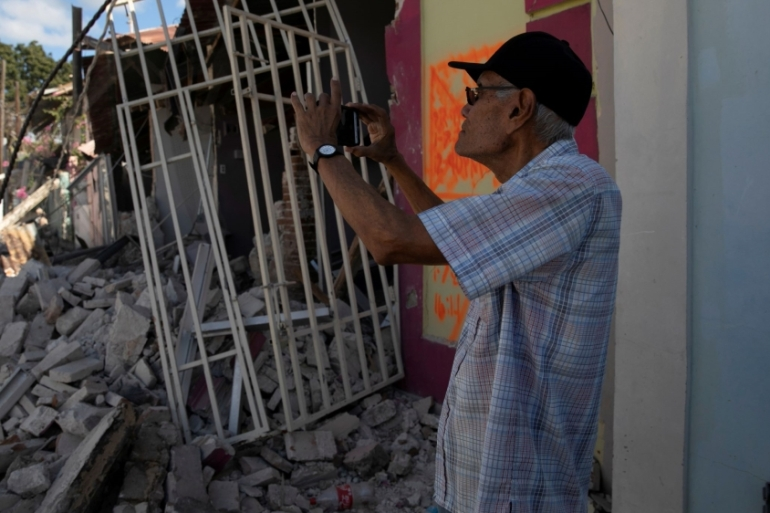 A man uses his phone to take photos of damaged houses after an earthquake in Guanica, Puerto Rico this week [File: Marco Bello/Reuters]