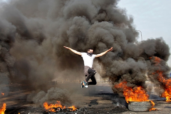 An anti-government protester jumps over burning tyres blocking a highway in Baghdad in January 2020 [File: Khalid Mohammed/AP Photo]