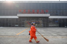 A cleaner walks past Sihui Long-Distance Bus Station in Beijing after the city halted the operation of interprovincial buses following the outbreak of the new coronavirus. [Thomas Peter/Reuters]
