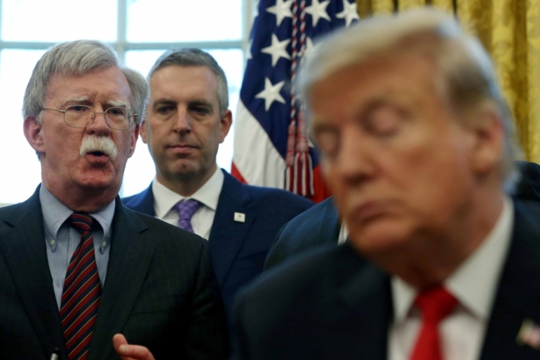 Trump listens as his then-National Security Adviser John Bolton speaks during a presidential memorandum [File: Leah Millis/Reuters]