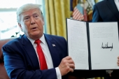 US President Donald Trump displays an executive order imposing fresh sanctions on Iran in the Oval Office of the White House in Washington, US, June 24, 2019 [Carlos Barria/Reuters]