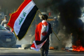 A demonstrator carries an Iraqi flag as he walks near burning tires, during an anti-government protest in Najaf, Iraq January 12, 2020. [Alaa al-Marjani/Reuters]