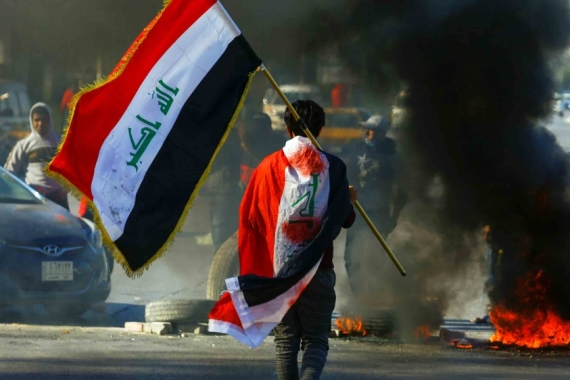 A demonstrator carries an Iraqi flag during an anti-government protest in Najaf [File: Alaa al-Marjani/Reuters]