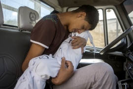 Mohammed Maadi holds his dead niece, two-year-old Jana, two days after she was killed when Israel bombed their family home in the Gaza Strip in August 2014 [Anne Paq/Al Jazeera]