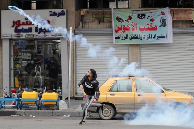 A demonstrator throws a tear gas canister back at the Iraqi security forces during ongoing anti-government protests in Baghdad [Thaier al-Sudani/Reuters]